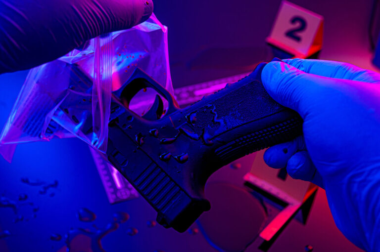 Forensic science, murder weapon and criminal investigation concept theme with detective wearing latex gloves bagging gun to send to lab in a dark crime scene illuminated by red and blue cop car lights