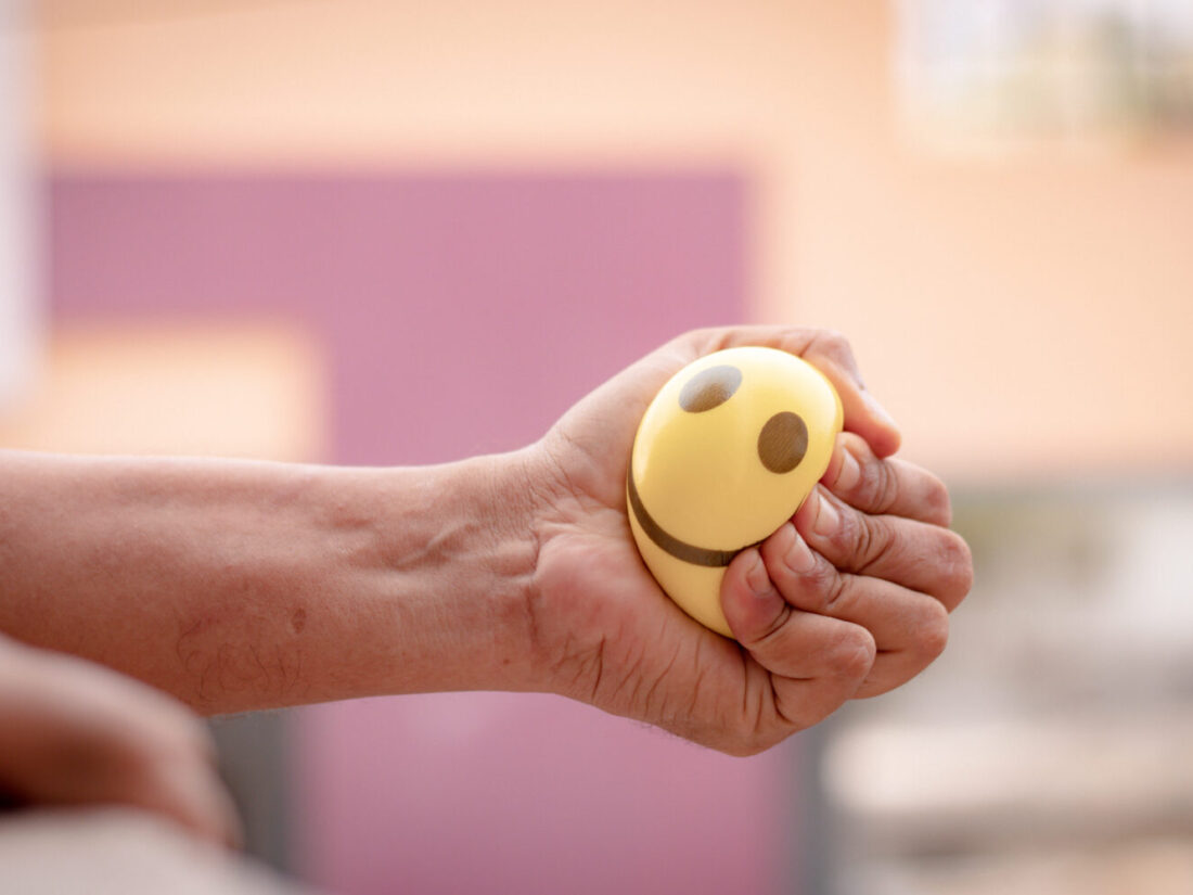 Hands squeezing or pressing stress ball at home to release stress concept of stress buster